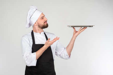 Chef cook holding an empty plate. Portrait of chef cook showing tray. Restaurant chef is demonstrating something. Concept - demonstration of dishes in restaurant. Restaurant menu. Guy in clothes cook