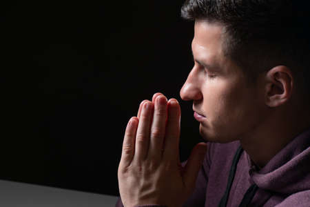 A man prays. The man closed his eyes and folded his hands in front of his chest. The concept of religion and faith. The guy prays to God. Believing man.