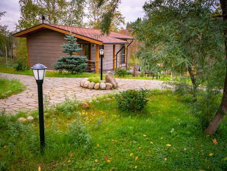 Wooden house in nature. Small cottage stands by the water. Concept - territory of a country villa. House far from the city. Concept - landscape design. Example of landscaping a villa. Stone path
