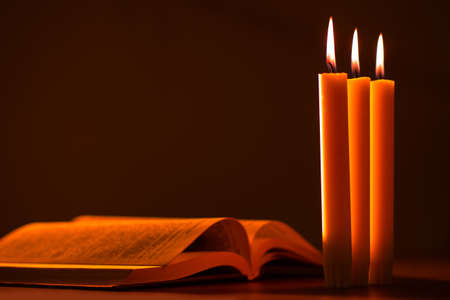 An open Bible and three candles in the warm light. communion with God. Religious reading. Christian sermon. Reading prayers over the dead. Prayer for the repose of the soul. RIP.