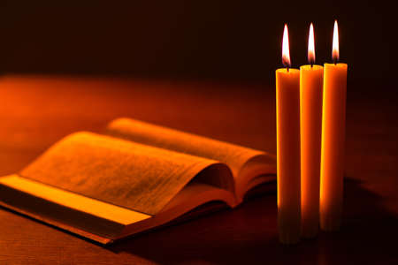 Christian faith. The Holy Bible and three burning candles on the table in the semi-darkness. Catholicism, Protestantism, Orthodoxy. appeal to God. Bible reading.