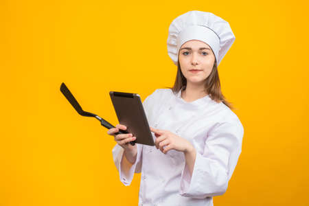 Cook Woman chef holding a tablet in her hands. Concept - online store for cooks. Cook wants order through tablet. Application with recipes. Book of Receptions. Girl in cook uniform. Chef Cooking food