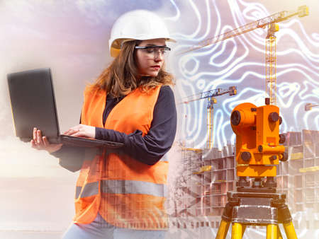 Geodesy. Surveyor. Girl works as surveyor. Builder is holding laptop. Concept - preparation of geodetic plans. Device for geodetic works. Topographic equipment. Construction of multi-storey buildings