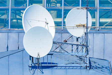Satellite television antennas. Round satellite dishes on roof of the building. Several television antennas are installed nearby. Equipment for receiving tv signal. Concept - satellite television