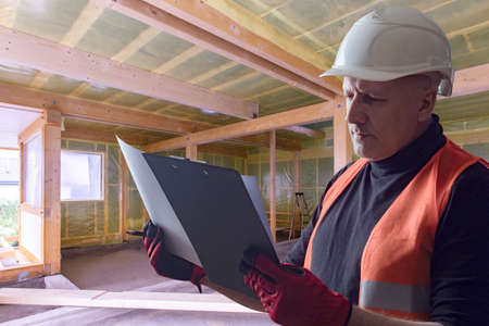 Repairman is studying a work plan. Repairman is reading paper. Repairman inside a house under construction. Repair and maintenance of wooden houses. Walls of wooden house are covered with film.