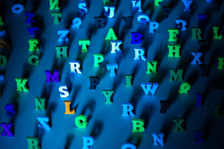 Multicolored letters of the alphabet. Chaotic English letters cast a shadow. Volumetric symbols on a blue background. Letters as a symbol of reading. Concept - reading English books and literature