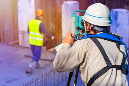 Surveying at a construction site. Builder with a tachometer. Man is measuring. Gyodetic research. Concept - sale of tachometers. Concept - construction quality control. Engineering work. Cadastre
