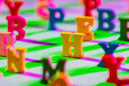 Three-dimensional letters are on table. Multicolored English letters as symbol of children ABC book. English symbols on green background. Concept - teaching to read. All letters except H are blurred.