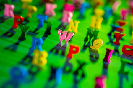 English 3D alphabet on a green background. Focusing on letters in center. Extreme letters of the alphabet are blurred. Three-dimensional Latin letters as a symbol of learning English. Stockfoto