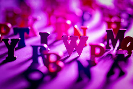 English alphabet letters close up. All letters except w are blurred. Early-colored letters in a chaotic arrangement. Front view. Concept - learning English. Latin alphabet as a symbol of education.
