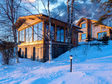 House christmas on a winter day. Birch trees next to wooden cottages. House christmas on snowy hills. Exterior house christmas. Two cottages for winter living. Country cottages with panoramic windows