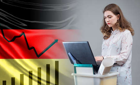 Unemployment line on background flag of Germany. Unemployment woman looking for in laptop. Box for personal items in front of a woman. Unemployment rate Germany. Looking for work on Internet 版權商用圖片