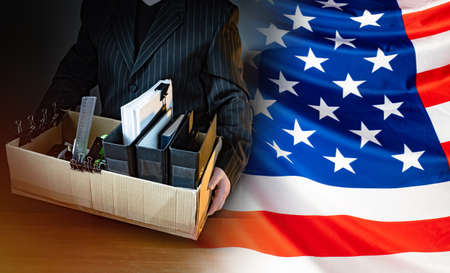 Unemployed. Man holds a box with personal belongings. USA flag. Concept - unemployed American. American was fired. USA resident is unemployed. Stationery in a cardboard box. American labor market 版權商用圖片