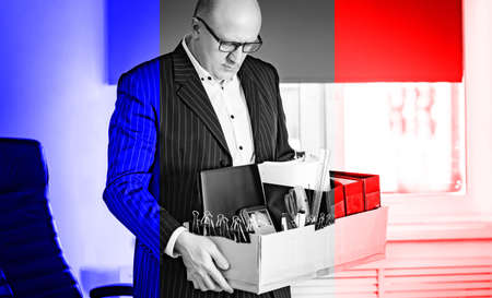 Dismissal. Man is saddened by loss of work. dismissal resident of France. Man in a suit holds a box in hands. Frenchman saddened by dismissal. Box a symbol of layoffs. France company employee fired 版權商用圖片