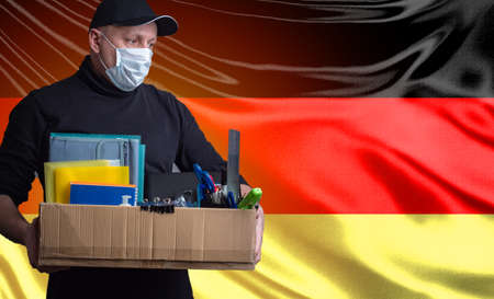Dismissed man in a medical mask. Unemployed man on background of flag of Germany. Cardboard box a symbol of job loss. Concept - layoffs due to coronavirus. Man came under contractions due to covid-19