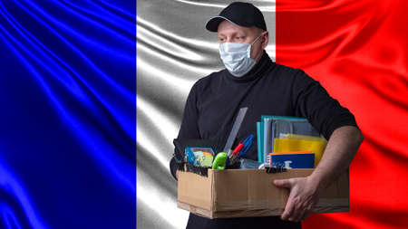 France. Unemployed man with a mask on his face. Unemployment in France due to epidemic. Unemployed holds a cardboard box. Man on background of flag France. Coronavirus cause of unemployment. Covid-19 版權商用圖片