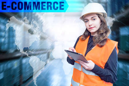 E-commerce inscription next to a world map. Woman works in a logistics company. E-commerce logistic. Logistics internet company. Concept - logistics business. Woman in work uniform looking at camera