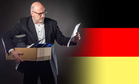 Dismissed man of Germany. Dismissed man holds a box. Unemployed next to flag of Germany. Dismissed man in a business suit. Concept - mass cuts in Germany. German reads a letter of resignation 版權商用圖片