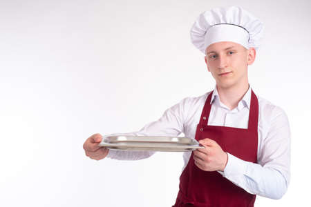 Chef cook man on a white background. Man holds an empty tray in front of him. Young man works as a cook. Concept - chef presents dish. Place for an inscription next to chef. Guy in cook hat.