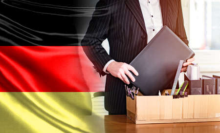 Dismissal in Germany. Man puts personal items in a box. Concept - massive dismissal. dismissal due to crisis in Germany. Box as a symbol of layoffs. Man picks up personal items from office. 版權商用圖片