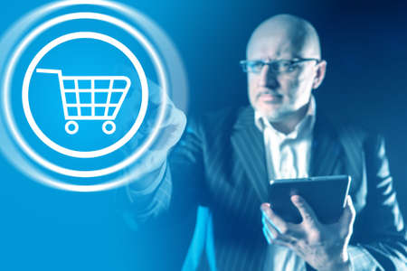 Businessman pressing button with a shopping cart. Online commerce symbol on a virtual screen. Concept - businessman makes purchases on Internet. Online shopping. Man in business suit buys on Internet