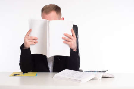 Man covers his face with paper. Accountant. Auditor examines the documents. Auditor is reading something. Consulting services. Concept - Businessman is studying company documentation.