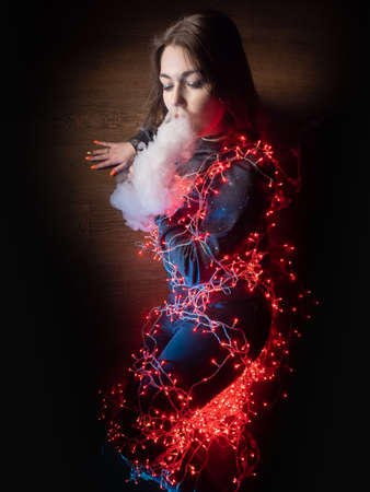 A girl smokes a VAPE on a dark background. Vaper woman is wrapped in a garland. The girl lies on the floor and lets out smoke from an electronic cigarette. Vapeshop concept.