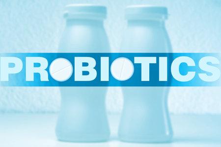 Probiotic yogurt. Logo of probiotics next to bottles of yogurt. Yogurt with probiotic bacteria. Sour-milk products with beneficial microorganisms. Sale of dietary supplements. Beneficial bacteria.