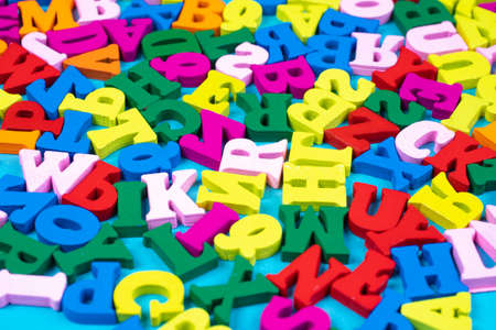 Different letters of the English alphabet. Bright Latin letters in a chaotic arrangement. Concept - learning English letters. The alphabet as a symbol of primary education. Primary school education