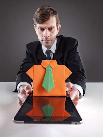 Businessman is engaged in selection of personnel. Man holds tablet in front of him. Figure of office worker made of paper symbolizes search for employees. Recruiter is looking for employees internet 스톡 콘텐츠