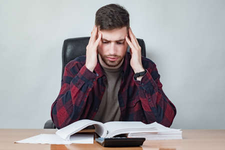 Upset man looks at a calculator. Guy is upset at the big expense. Human is holding his head. Man rereads the contract. Concept - guy is studying a loan agreement. Concept - thinks how to cut costs.