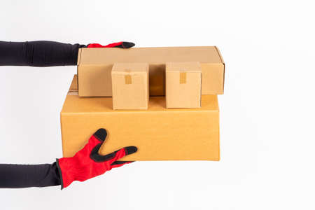 Several boxes in hands of courier. Courier hands close up. Concept - delivery of goods by courier service. Unlabeled boxes white background. Deliverymanhands over order. Delivery from online store Stockfoto