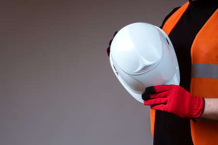 White helmet in hands of a worker. Protective helmet in hands of builder. Concept - safety at a construction site. Man in orange vest. Sale of building uniforms. Place for inscription next to builder
