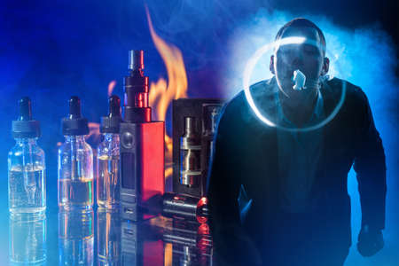 Vaper. Create shapes from cigarette smoke. Vape device next to vaping juices. Vape oils are in bottles. Young vaper on a dark background. Guy blows vapor from a cigarette. Electronic cigarettes.