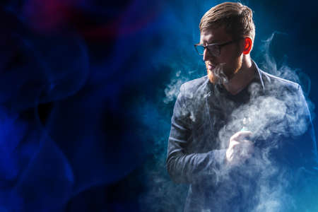 Vape. Vaper in the clouds of smoke. Human with a vape device in his hands. Man with a vape device on a dark background. Vaper with an electronic cigarette. Concept - sale of devices for a vaper. Imagens