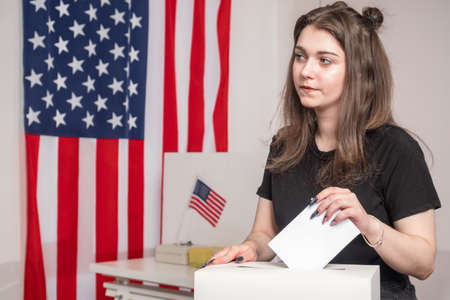Election in United States of America. Woman Voter in booths polling station USA. Throws a bulletin into ballot box. USA presidential election campaign. Voting for President of US at polling station