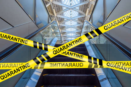 Entrance to the escalator is closed. Inscription quarantine on a yellow ribbon. Concept - closure of the shopping center due to quarantine. Airport closure due to pandemic. Threat of infection.