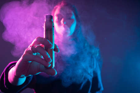 Vape. Vaper. Vaping. Woman holds out an electronic cigarette. Concept - girl gives a try a vape device. Concept - alternative to cigarettes. Smoking electronic cigarettes. Concept - vaper shop. E-cig