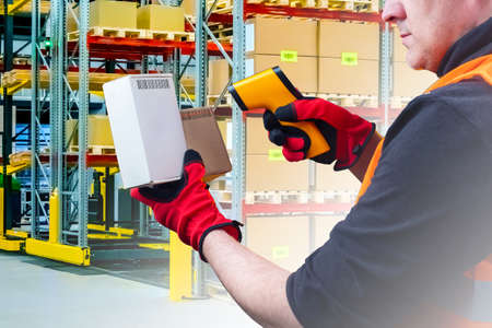 Man works in a warehouse. Human scans barcodes on boxes. Concept - career of a warehouse worker. Man scans a barcode before sending it. Concept - modern logistics center. Concept - dropshipping.