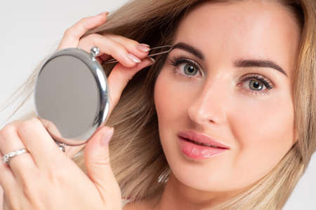 Eyebrow correction. Girl with tweezers and a mirror in her hands. Girl plucks her eyebrows. A woman changes the shape of her eyebrows. Beautiful girl with tweezers and a mirror looks at the camera.