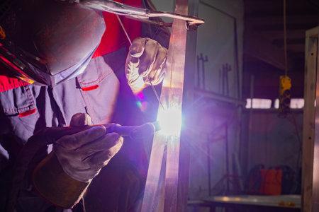 Welding work. Metal welding. Worker welds metal parts in the shop. A worker wearing an industrial uniform and a welded iron mask in the welding plants.