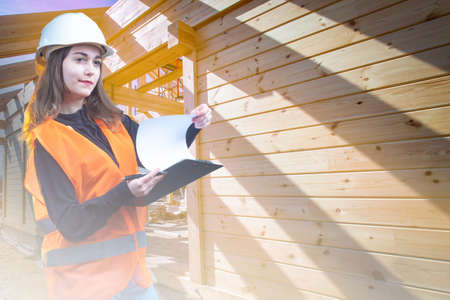 Young woman works in the construction industry. Concept - student is studying to be an architect. Girl inspects the building site. Builder inside the building under construction. Wooden houses. Reklamní fotografie