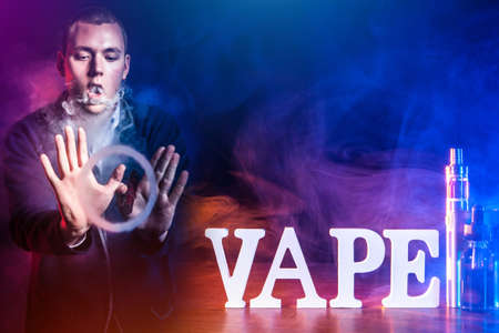 Vaping. Vape logo on the table. Wapit shows smoke tricks. Concept - vaper stuntman. Young guy is vaping. Man made a ring of steam. Concept - gift for the vaper. Sale of vape accessories.