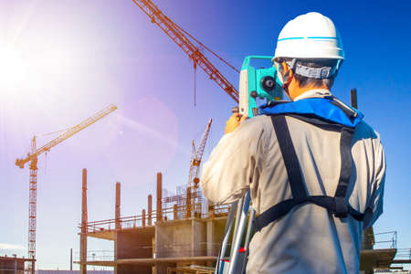 Gyodesist controls the work of builders. Builder with tachometer next to a construction site. Concept - codaster works. Concept - training for a surveyor. Man with a tachometer. Surveying Equipment.