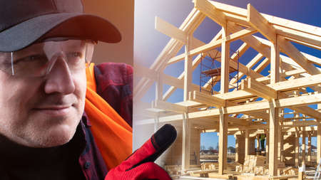Builder points a finger at the photo. Image of a house under construction. Frame of wooden house on sky background. Concept - business in field of construction. Man provides construction services.