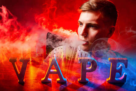Vaping. Vape logo next to a young guy. Vaper in clouds of smoke. Lot of smoke next to vape logo. Man is engaged in vaping. Concept - Vape bar. Electronic cigarette smoking. Sale of sets for vapers.