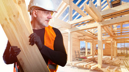 Builder carries several boards. Man works at a construction site. Man is building a house. Builder near frame of the house. Construction of the house. Concept - sale of frame houses. Career builder