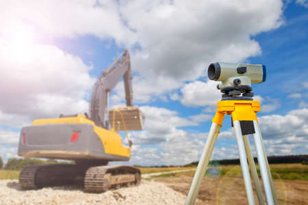 Optical level next to excavator. Concept - an excavator clears places for construction. Preparation of site for construction of the house. Optical level on the sky background. Gyodetic preparation.