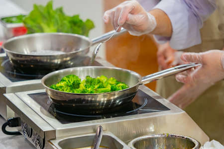 The chef is frying broccoli in a sauce. Recipes for vegetable dishes. Side dishes of cabbage. Work as a chef in a restaurant. Professional cooking. Vegetarian diet.