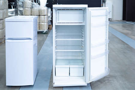 Refrigerator. Two refrigerators stand nearby. Equipment for cooling. Concept - appliances for the kitchen. Concept - a warehouse of household appliances. Open fridge in stock. Freezer